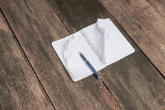 Notebook crumpled paper wrinkled blank  white  on the desk Stock Image