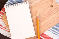 Notebook for culinary recipes on a cutting board with napkin. Stock Photos