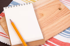 Notebook for culinary recipes on a cutting board with napkin. Stock Image