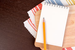 Notebook for culinary recipes on a cutting board with napkin. Open recipe book on wooden background Royalty Free Stock Image