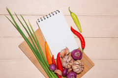 Notebook for culinary recipes with fresh organic vegetables.  Stock Photo