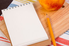 Notebook for culinary recipes with old apple on a cutting board with napkin. Stock Photos