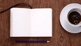 Notebook and cup being filled with coffee stock footage