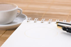 Notebook and cup of coffee Stock Images