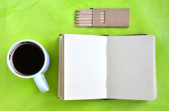 Notebook, cup of coffee and crayons on green background. Notebook (blank page), cup of coffee and crayons on green background. Flat lay Royalty Free Stock Image