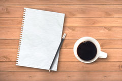 Notebook and cup of coffee on desk Stock Photos