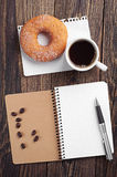 Notebook and cup of coffee with donut Stock Photo