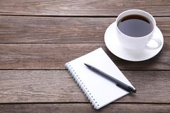 Notebook and cup of coffee on grey wooden background royalty free stock photo