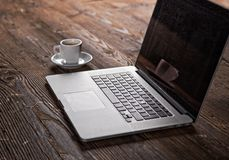 Notebook with cup of coffee on wooden table Royalty Free Stock Photography