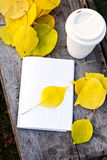 Notebook, cup of coffee and yellow autumn leaves Stock Image