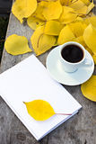 Notebook, cup of coffee and yellow autumn leaves Royalty Free Stock Photos