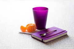 Notebook, cup, tangerine and teaspoon Royalty Free Stock Photos