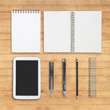 Notebook, cutter, pen, pencil  and tablet on wood table Royalty Free Stock Images