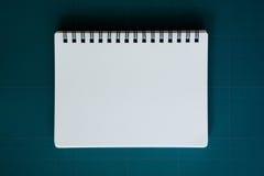 Notebook on cutting mat. Notebook on blue cutting mat stock photo