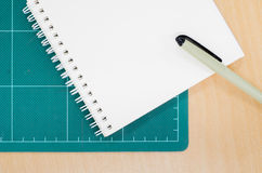 Notebook with cutting mat on wooden table, blank notebook. Post it note, stationary, office Stock Images