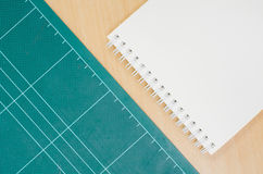 Notebook with cutting mat on wooden table, blank notebook, post. It note, stationary, office Stock Photos