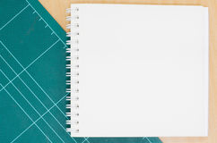 Notebook with cutting mat on wooden table, blank notebook, post. It note, stationary, office royalty free illustration