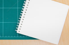 Notebook with cutting mat on wooden table, blank notebook, post Royalty Free Stock Image