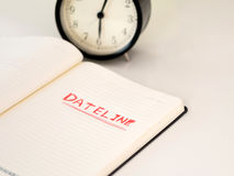 Notebook with Dateline written with a clock. Blank notebook with Dateline written with a clock Royalty Free Stock Photos