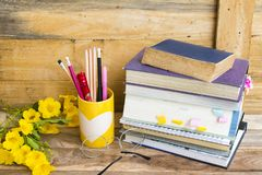 Notebook ,dictionary english and all book for study. Of student  with stationary ,yellow flowers decoration on background wooden royalty free stock photo