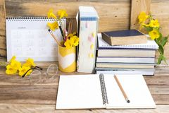 Notebook ,dictionary english and all book for study. Of student  with stationary ,yellow flowers decoration on background wooden stock photos