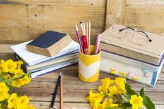 Notebook ,dictionary english and all book for study. Of student  with stationary ,yellow flowers decoration on background wooden stock images