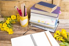 Notebook ,dictionary english and all book for study. Of student  with stationary ,yellow flowers decoration on background wooden royalty free stock image