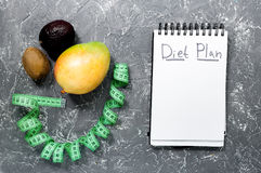 Notebook for diet plan, fruits mango, kiwi and measuring tape on grey stone table top view mock up Stock Photo