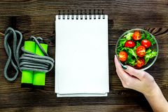 Notebook for diet plan, hand is holding salad with fresh product. S and jump rope on table top view Stock Photo