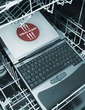 Notebook in dishwasher from above  - virus alert Royalty Free Stock Image