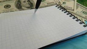 Notebook dollars, pen falls, slow-motion economy. Notebook dollars, pen falls, slow-motion office economy stock footage