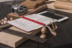 notebook with drawings, pencil, tape measure, smartphone, square and plane on a black table royalty free stock image