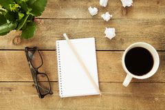 Notebook with drinking coffee on wooden table Royalty Free Stock Photo