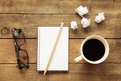 Notebook with drinking coffee on wooden table Stock Images