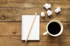 Notebook with drinking coffee on wooden table Stock Image