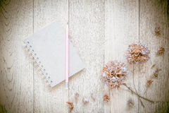 Notebook and Dry flowers on old wood background. Vintage Style Royalty Free Stock Photography