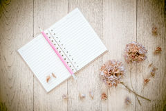 Notebook and Dry flowers on old wood background. Royalty Free Stock Photos