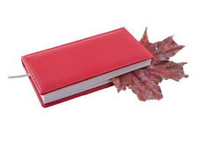 Notebook and dry leaf. Autumn leaves in red notebook Stock Images