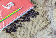 Notebook,earphone and pencil on wooden table background Stock Photos