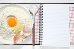 Notebook, egg, flour and spoon Stock Photography