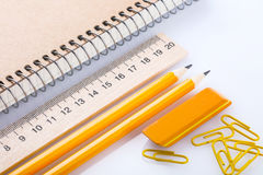 Notebook, eraser, ruler, pencil and paperclips Stock Images