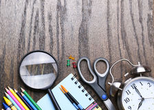 Notebook, exercise book, scissors, alarm clock and pencils Stock Image