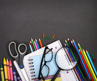 Notebook, exercise book, scissors and pencils on black board Stock Image