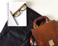 Notebook  eye glasses pencil and leather bag on white background Stock Photography