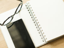 Notebook eyeglass and black smart phone on brown table. Royalty Free Stock Photos