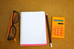 Notebook, eyeglass and calculator on wooden background for financial concept. Blank Notebook, eyeglass and calculator on wooden background for financial conceptn stock image
