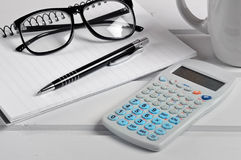 Notebook with eyeglasses,calculator and pen Stock Photos