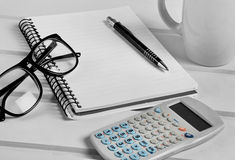 Notebook with eyeglasses and calculator Stock Images