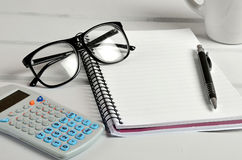 Notebook with eyeglasses and calculator Royalty Free Stock Images