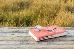 Notebook and eyeglasses on wooden background Stock Images